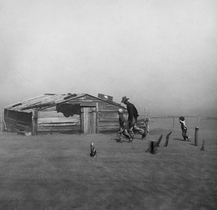 Farmer and sons walking in the face of a dust storm. Cimarron County, Oklahoma. 1936